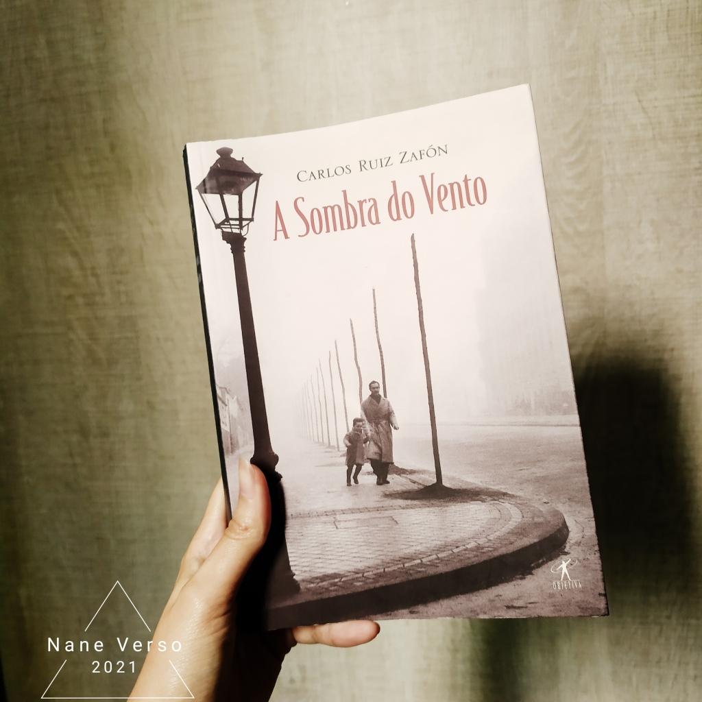 Uma mão segura o livro A sombra do vento em frente a um fundo bege. A foto está com algumas sombras. No canto esquerdo, a marca d'água do blog/instagram: Nane Verso 2021 dentro de um triângulo.